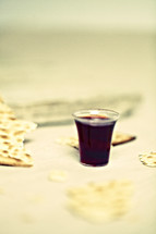 Communion cup filled with wine and broken pieces of an unleavened cracker