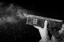 blowing dust off a Bible
