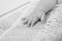 An infant's hand laying on an open bible