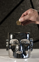 Mind on Money; hand holding coin (dollar) above a metal head.