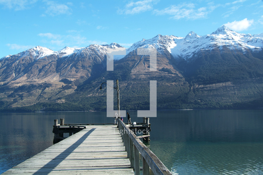 pier over water with snow covered mountain range