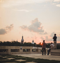 Men on a roof looking at a skyline of mosques and domes at sunset.