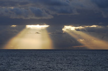 Sun light shining through dark clouds over the ocean. Sunrays radiating from behind storm clouds.