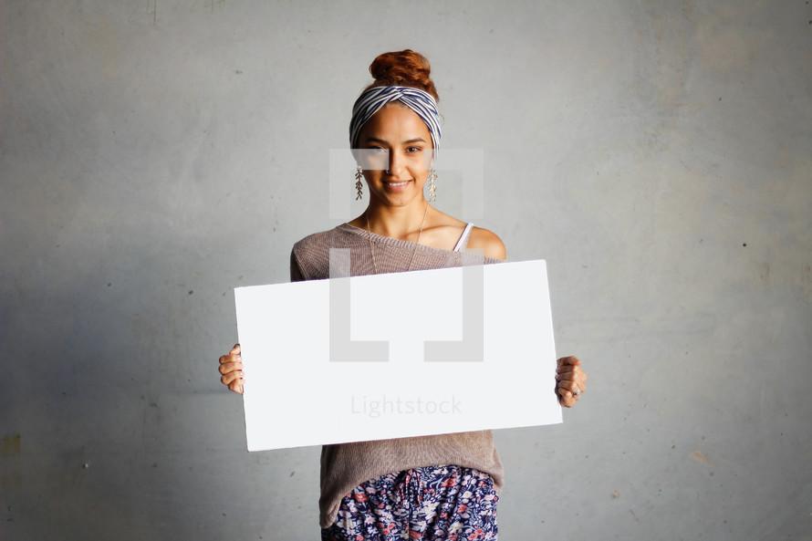 a teen girl holding a blank sign