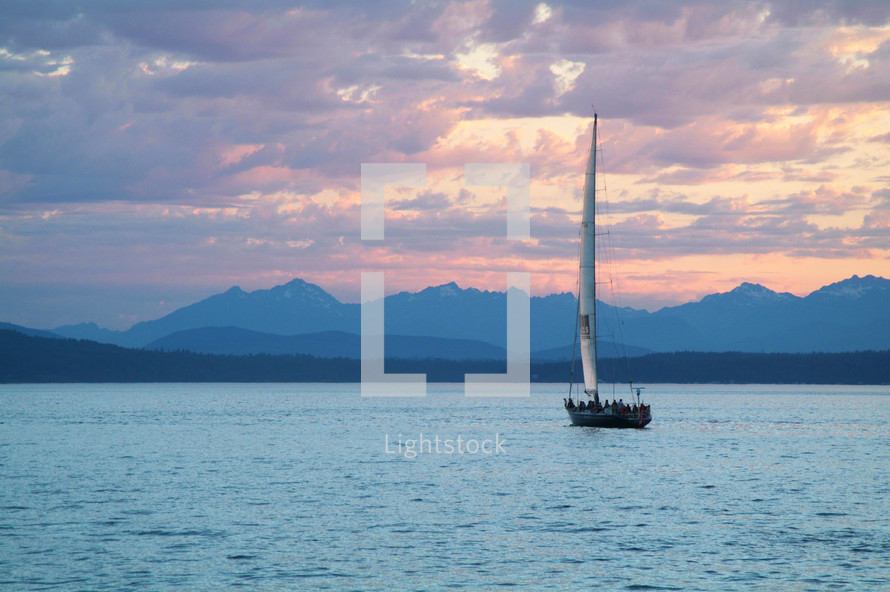 A sailboat on a lake surrounded by mountains.