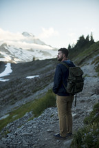 a man backpacking through mountain landscape
