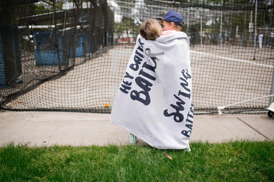 kids wrapped in a blanket at a batting cage