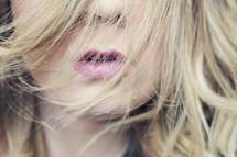 a woman's lips through her hair