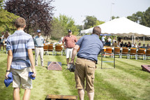 people playing corn hole at a picnic