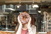 a woman holding a giant donut in front of her face