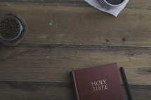 coffee beans in a mason jar, coffee mug on a napkin, and Holy Bible on a table