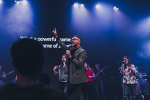worship leader speaking and singing to a congregation