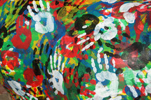 A background of colorful overlapping hand prints showing unity, harmony and cooperation alongside diversity