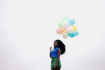 African American woman holding balloons