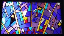 A colorful stained glass window with blue, lavender, purple, red and gold and symbols adorn a church worship center in a prayer chapel.