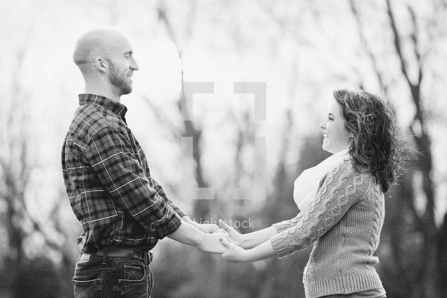 Smiling couple holding hands outdoors.