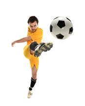 Young man in a yellow soccer uniform kicking a soccer ball