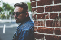 man in sunglasses leaning against a brick wall