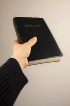 a hand holding out a Bible