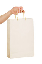 Hand holding a white paper bag with handles.