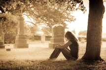woman sitting in front of a tree in a cemetery grieving