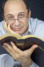 a man in glasses reading the pages of a Bible