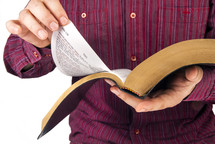 man turning the pages of a Bible