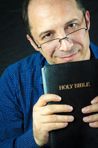 a man in glasses holding a Bible