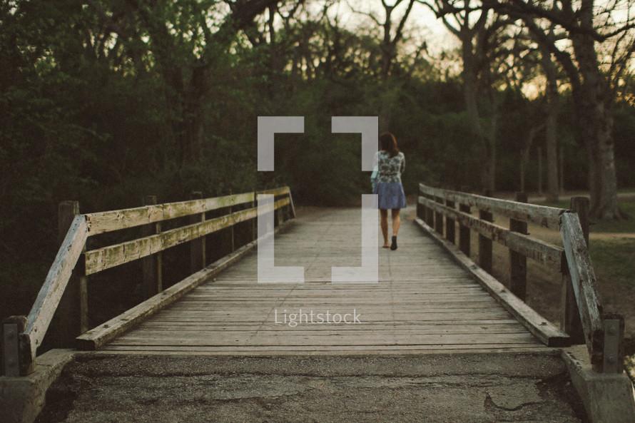 woman walking across a wooden footbridge