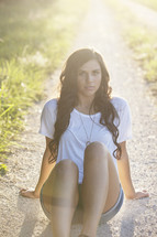woman sitting on a dirt road under the glow of sunlight