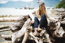 a woman sitting on a pile of driftwood on a beach
