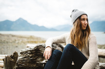 woman in a wool cap sitting on driftwood on a beach