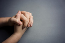 praying hands against a gray background