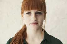 stoic face of a young red headed woman
