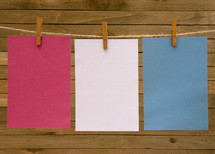 red, white, and blue paper on a clothesline