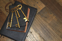 Large bunch of keys on a Bible, laid on a wooden desk