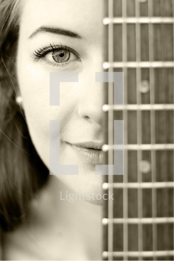 woman peeking from behind a guitar neck