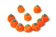 Orange gumdrop candy pumpkins arranged to form a smiley face.