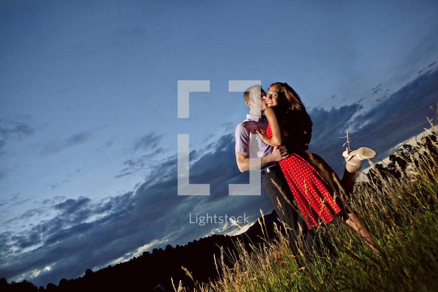 couple embracing, outdoors on hillside