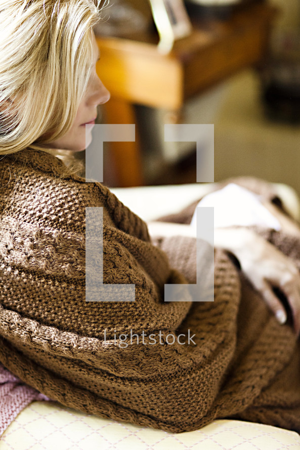 A sitting woman wrapped in a brown blanket.