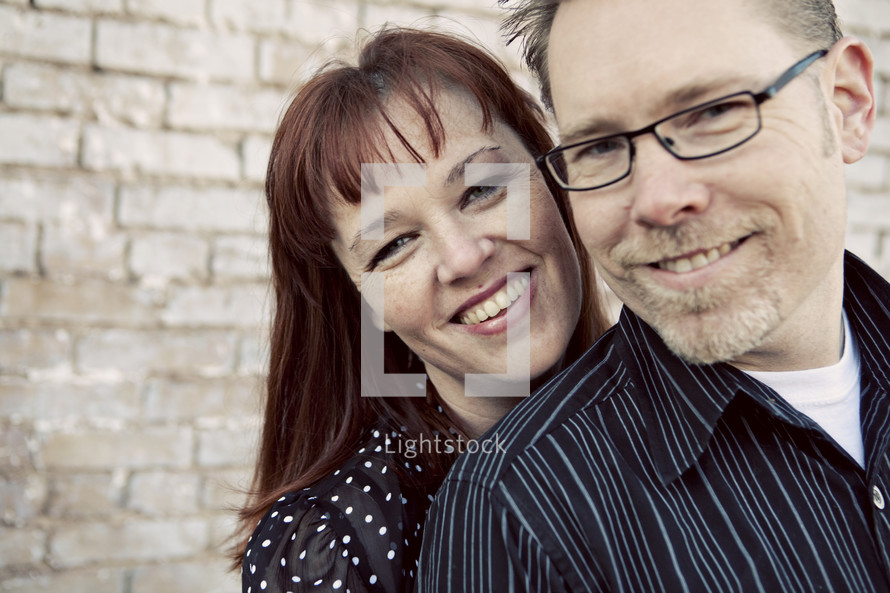 Couple in front of brick wall smiling
