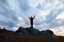 Silhouette of a man with arms raised in praise, standing on a rock outside under the clouds.
