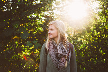 blonde woman standing outdoors and a burst of sunlight