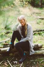 blonde woman sitting on a fallen tree