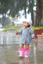 Toddler girl wearing coat, hat and rainboots in rain on wet sidewalk.