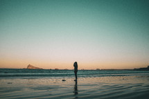 silhouette of a person taking pictures on a beach at sunset