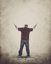 man standing on parched soil with his hands raised in worship to God