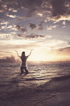 woman standing in the ocean with her hands raised in worship to God