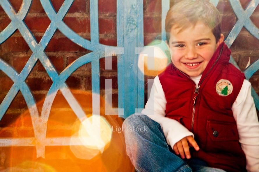 boy sitting in front of blue door