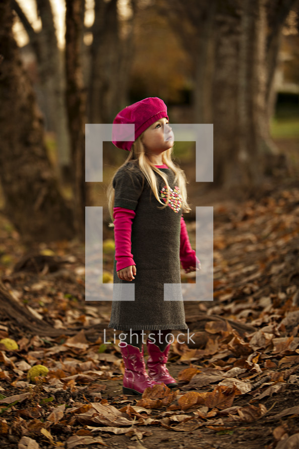 girl stand amid leaves